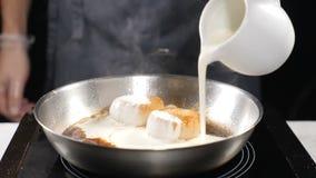 Cozinhando o marisco Conceito saudável do alimento Cozinheiro chefe nas luvas que cozinha as vieiras que derramam o molho de crem filme