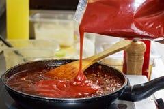 Cozinhando o molho de tomate na bandeja imagens de stock