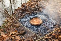 Cozinhando o pão em carvões do fogo na noite foto de stock