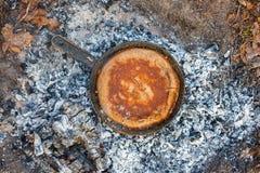 Cozinhando o pão em carvões do fogo na noite foto de stock royalty free