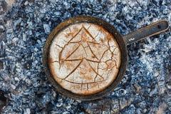 Cozinhando o pão em carvões do fogo na noite imagem de stock royalty free