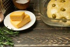 Cozinhando o pão italiano de Focaccia com verdes das azeitonas, da manteiga, do queijo e dos alecrins A receita caseiro do cozinh fotos de stock royalty free
