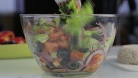 Cozinhando o ponto baixo do vegetariano - salada grega da caloria, as mãos da mulher que lanç a salada da vídeos de arquivo
