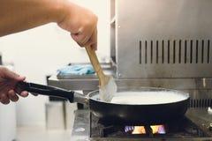 Cozinhando o queijo na bandeja pelas mãos do cozinheiro chefe no fogão de gás Imagens de Stock