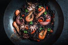 Cozinhando os espaguetes pretos com o marisco feito do polvo, camarões do tigre Imagens de Stock Royalty Free