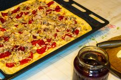 cozinhando a pizza caseiro com pimentas, ameixas, presunto, salsicha, queijo e especiarias, close up fotos de stock