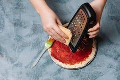 Cozinhando a pizza italiana com tomates, galinha, azeitonas no fundo de madeira Molho de tomate na massa pela mão da mulher imagens de stock
