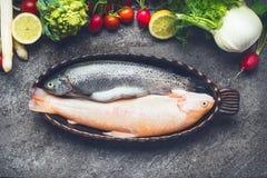 Cozinhando a preparação de pratos de peixes com os dois ingredientes crus da truta e dos vegetais no fundo concreto cinzento Foto de Stock