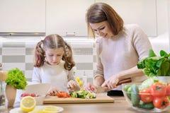 Cozinhando a refei??o saud?vel da casa pela fam?lia A m?e e a filha cortaram vegetais em casa na cozinha para a salada imagem de stock royalty free
