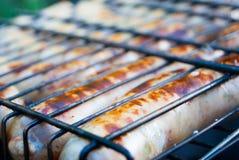 Cozinhando salsichas alemãs nos carvões Piquenique imagens de stock royalty free