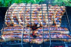 Cozinhando salsichas alemãs nos carvões Piquenique fotos de stock royalty free