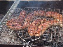 Cozinhando salsichas na grade Almoço na natureza Imagens de Stock