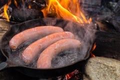 Cozinhando salsichas no frigideira do ferro fundido na fogueira ao acampar Bom e alimento positivo da fogueira Fotografia de Stock