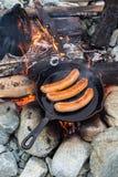 Cozinhando salsichas no frigideira do ferro fundido na fogueira ao acampar Bom e alimento positivo da fogueira Fotos de Stock