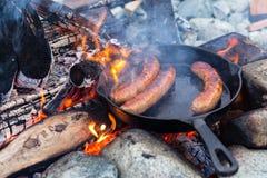 Cozinhando salsichas no frigideira do ferro fundido na fogueira ao acampar Bom e alimento positivo da fogueira Fotos de Stock Royalty Free
