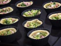 Cozinhando tartlets caseiros com bacon, alho-porros, brócolis e queijo Fotografia de Stock