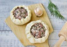 Cozinhando tortas com carne e cebolas Brancos em uma placa de corte fotografia de stock royalty free