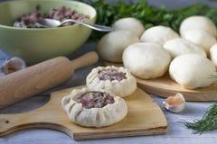 Cozinhando tortas com carne e cebolas Brancos em uma placa de corte imagem de stock royalty free