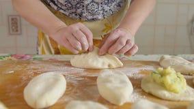 Cozinhando tortas A mulher cola a massa com enchimento para dentro video estoque