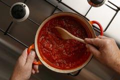 Cozinhando um molho de tomate tradicional do gormet e uma colher de madeira, em um hob inoxidável do roubo foto de stock royalty free