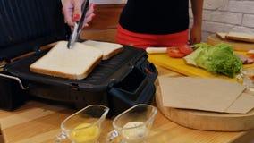 Cozinhando um sanduíche na cozinha As mãos com tenazes de brasa tomam o pão branco do brinde de um suporte de madeira e colocam-n filme
