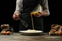 cozinhar O cozinheiro cozinha a massa para a massa, pizza, pão Põe um ovo batido na farinha Alimento delicioso, receitas, cozinha foto de stock royalty free