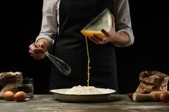 cozinhar O cozinheiro cozinha a massa para a massa, pizza, pão Põe um ovo batido na farinha Alimento delicioso, receitas, cozinha foto de stock