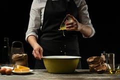 cozinhar O cozinheiro cozinha a massa para a massa, pizza, pão Põe um ovo batido na farinha Alimento delicioso, receitas, cozinha imagens de stock