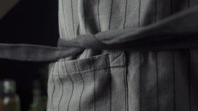 Cozinhe a amarração de um avental da cozinha na cozinha vídeos de arquivo