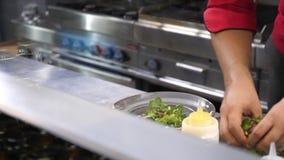 Cozinhe as mãos na cozinha do restaurante que prepara uma placa para clientes video estoque
