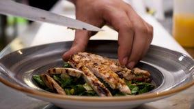 Cozinhe as mãos que colocam a carne grelhada fresca na placa com salada do abacate filme