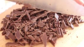 Cozinhe as mãos que cortam a barra de chocolate com uma faca de cozinha na placa de corte fotografia de stock royalty free