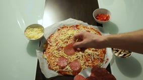 Cozinhe a colocação do salame sobre o queijo sobre uma pizza crua vídeos de arquivo