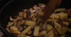 Cozinhe com a forquilha de madeira que frita as batatas na frigideira filme
