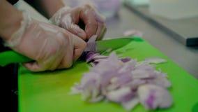 Cozinhe corta muito rapidamente uma curva roxa, em uma placa de corte filme