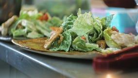 Cozinhe em uma cozinha do restaurante que prepara uma salada filme