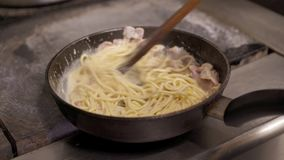 Cozinhe guardar a agitação dos espaguetes com o molho de queijo e o bacon desbastado que fritam na bandeja quente video estoque