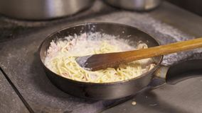 Cozinhe guardar a agitação dos espaguetes com o molho de queijo e o bacon desbastado que fritam na bandeja quente vídeos de arquivo