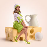 Cozinhe a menina que senta-se em uma parte de queijo Imagem de Stock
