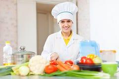 Mulher do cozinheiro em vegetais uniformes do corte Fotos de Stock Royalty Free