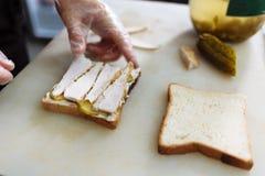 Cozinhe nas luvas do polietileno que fazem um sandu?che em uma placa branca foto de stock royalty free