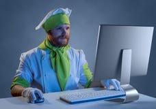 Cozinhe o cozinheiro chefe que trabalha em um computador com teclado e rato Imagens de Stock