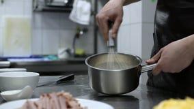 Cozinhe o creme e os ovos de chicoteamento das mãos em uma bandeja vídeos de arquivo