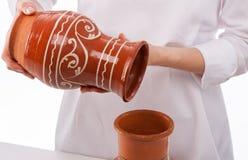 Cozinhe o derramamento de algo no jarro da argila Fotografia de Stock