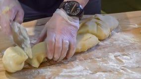 Cozinhe o homem amassa a massa com suas mãos nas luvas para o close-up de cozimento filme