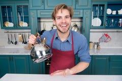 Cozinhe o homem na camisa azul, sorriso vermelho do avental com chaleira Fotografia de Stock