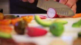 Cozinhe o rabanete do corte na placa de corte, mudança dinâmica do foco, close up filme