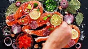 Cozinhe a preparação de partes cruas de salmões vermelhos dos peixes, polvilhe-a com os temperos, sésamo, vista superior video estoque