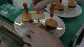 Cozinhe a terminação de um mini hamburguer perfurando o com um palito vídeos de arquivo