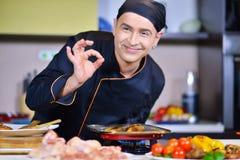 Cozinheiro alegre do cozinheiro chefe que cozinha e que mostra o sinal aprovado na cozinha Imagem de Stock Royalty Free